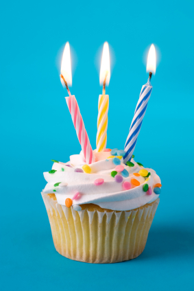 A birthday cupcake with three lighted candles.
